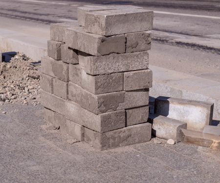 Pavement stones for footpath stacked near the road. construction, industrial. Reklamní fotografie