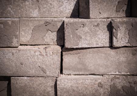 stack of gray pavement cobblestones, bricks. vignetted texture, construction.