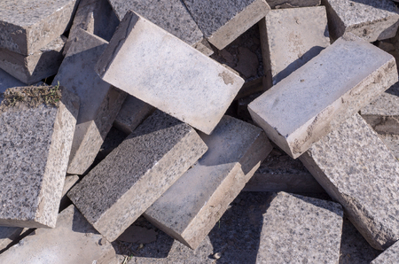 Pile of dirty gray curb bricks. background, texture.
