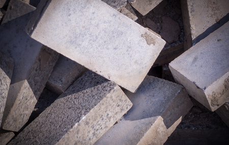 Pile of dirty gray curb bricks. background, vignetted texture. Reklamní fotografie