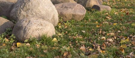 large stones and boulders with fallen leaves around in city part during autumn. nature, seasonal