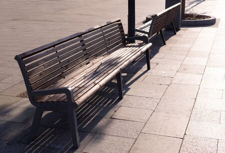 brown wooden bench on the street at sunset. furniture, city.
