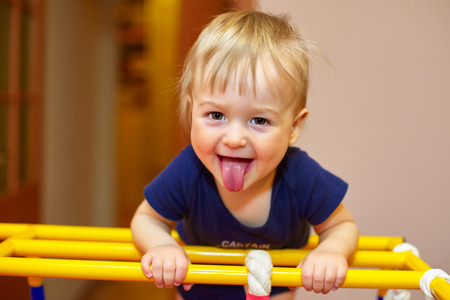 impish: Small boy does home fitness and puts out his tongue Stock Photo