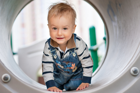 impish: Small boy climbed in the playground tube Stock Photo