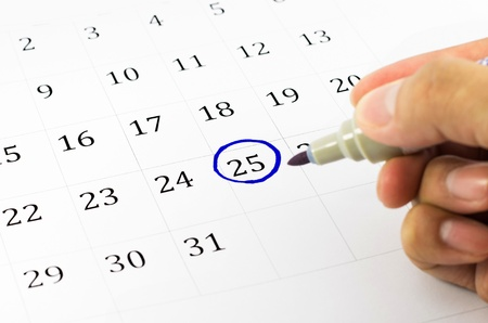 green dates: Blue circle. Mark on the calendar at 25. Stock Photo