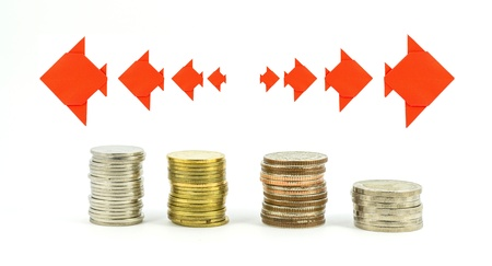 stacks of coins step thai baht with origami fish arrow on white background photo