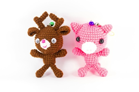 toys pattern: handmade crochet brown deer and pink pig doll on white background