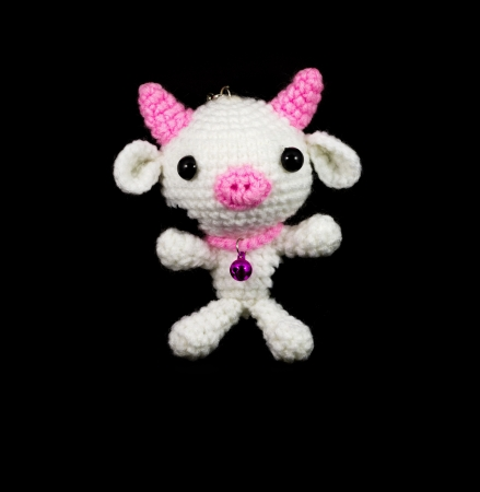 handmade crochet white pig with pink nose doll on black background photo