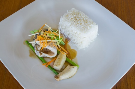 serv: grilled fillet of seabass with teriyaki sauce, serv with stream rice on wood table