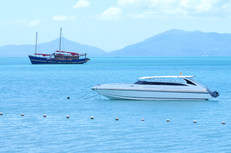 yacht speed boat and traditional boat on the sea with mountain background photo