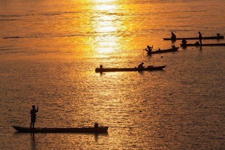 Many Fisherman paddling a Rowboats for fishing when sunset, Silhouette photo