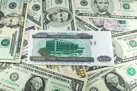 riel: myanmar kyats on many dollars background