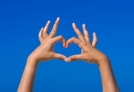 Girl hands forming be heart for love with blue sky photo