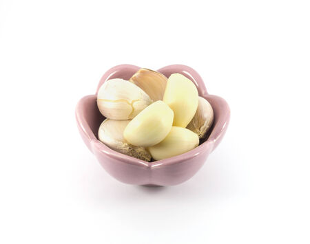 Fresh garlic isolated in pink cup on white background photo