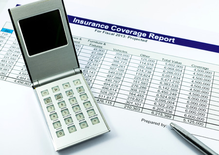 insurance coverage report with calculator and pen for business photo