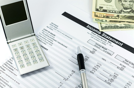 income statement report with calculator, pen and usd money for business photo
