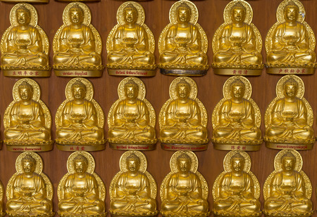 veneration: close up a part of ten thousand golden buddhas lined up along the wall of chinese temple, thailand