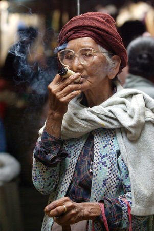 cheroot: BAGAN, MYANMAR- JAN 4: An unidentified woman smoking a cheroot cigar in market at bagan, Myanmar on January 4, 2011. A cheroot is a cigar made principally by dried fruits and little bit of tobacco Editorial