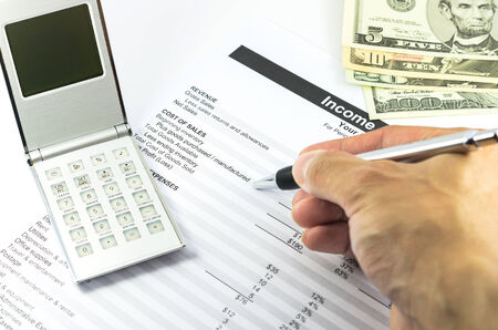 mark on income statement report with calculator, pen and usd money for business photo