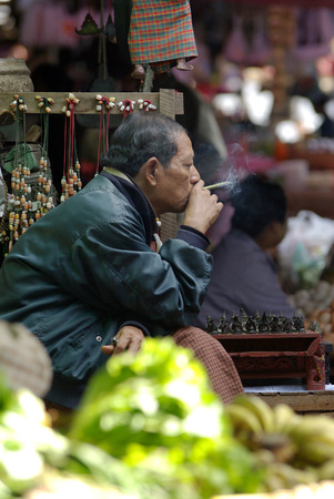 cheroot: BAGAN, MYANMAR- JAN 4: An unidentified Burmese man smoking a cheroot cigar in market at bagan, Myanmar on January 4, 2011. A cheroot is a cigar made principally by dried fruits and little bit of tobacco