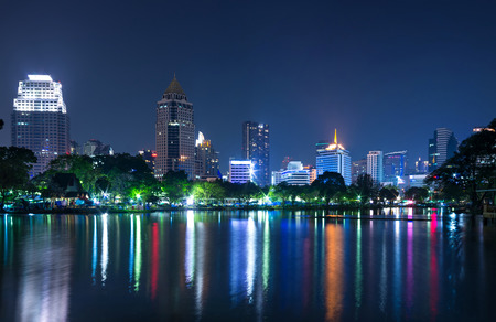 cityscape reflect with lake view in the park at twilight time. photo