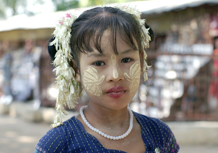 MANDALAY, MYANMAR - JANUARY 03: Unidentified Burmese girl with traditional thanaka on her face on January 03, 2011 in Mandalay, Myanmar. Thanaka is a yellowish-white cosmetic paste made from ground bark