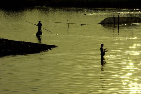 traditional fishing during sunset, U-Ben Bridge, Mandalay, Myanmar photo