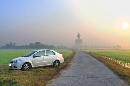 The Big Buddha at Wat Muang Temple with white color car, fog and tree when sunrise, Angthong, Thailand photo