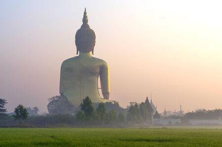 The Big Buddha at Wat Muang Temple with fog and tree, Angthong, Thailand photo