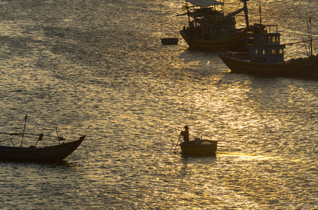 padding: fisherman padding the traditional boat at village of Mui Ne, Vietnam Stock Photo