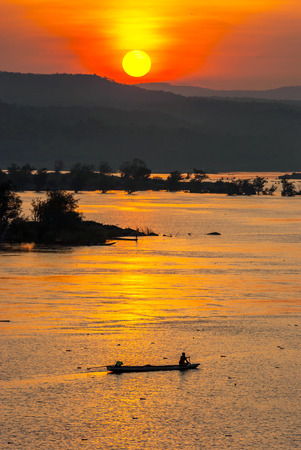 sihlouette: Fisherman paddling rowboat to fishing with sunset, Silhouette Stock Photo