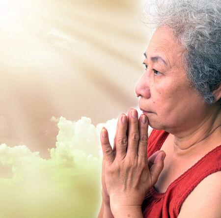 sun ray: Old woman praying with sun ray