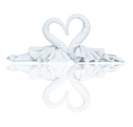 Two white towels swans with heart on white background photo
