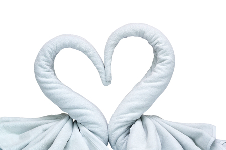 Close up two white towels swans with heart on white background photo