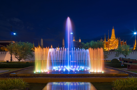 Waterworks with Grand palace background and reflection at twilight time in Bangkok, Thailand photo