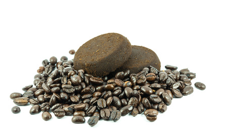 particulate: used ground coffee tablet with roasted coffee beans on white background Stock Photo