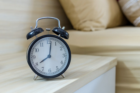 Retro alarm clock on the table beside bed at morning Stock Photo