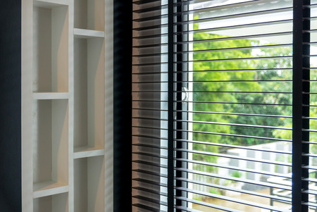 wakening: blinds inside a window being opened with bedroom interior