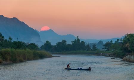 sihlouette: Fisherman paddling rowboat to fishing when sunset, vangvieng, Laos Stock Photo