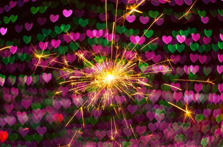 sparklers: Electric sparklers with heart bokeh background