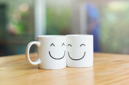 filiżanka kawy: Dwa szczęśliwy filiżanki na stole drewna, o koncepcji miłości Zdjęcie Seryjne
