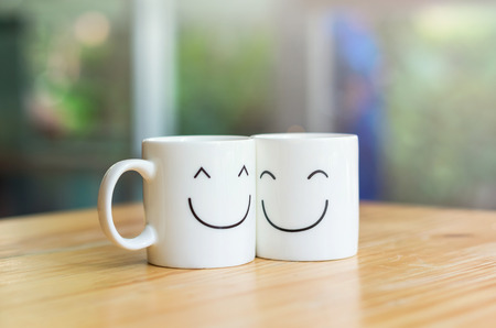 mug: Two happy cups on the wood table, about love concept