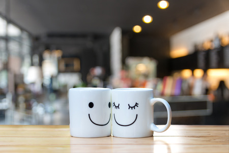 idea: Two happy cups on coffee store blur background