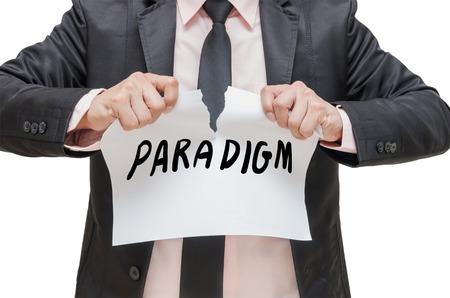 paradigma: Hombre de negocios que rasga el cartel PARADIGMA en el fondo blanco