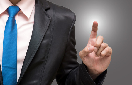 navy blue suit: Businessman pointing or touching on gray background Stock Photo