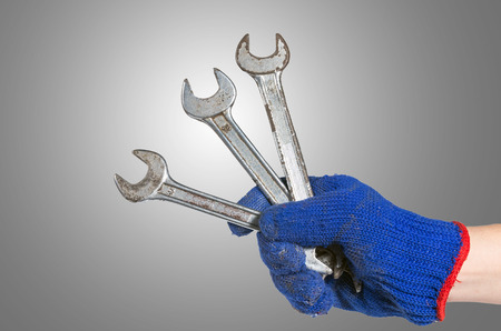 hand holding the wrench on gray background. industrial equipment