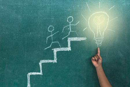 hand showing the idea of success on blackboard background Banco de Imagens