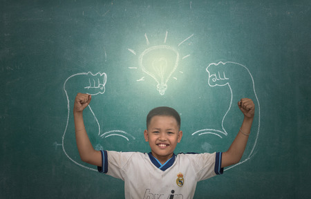 Asian strong children against blackboard in classroom photo