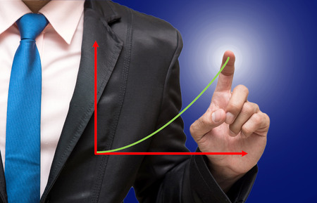Businessman pointing or touching with upper graph on dark blue background photo