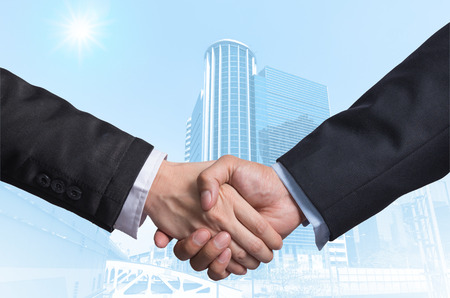 contact business: Hand shake between a businessman on Modern business building glass area background